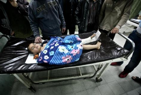 A wounded Palestinian child is checked by doctors at a hospital in Beit Lahia in the northern Gaza, on March 11, 2012, following a fresh Israeli air raid. (Ali Jadallah / APA images)